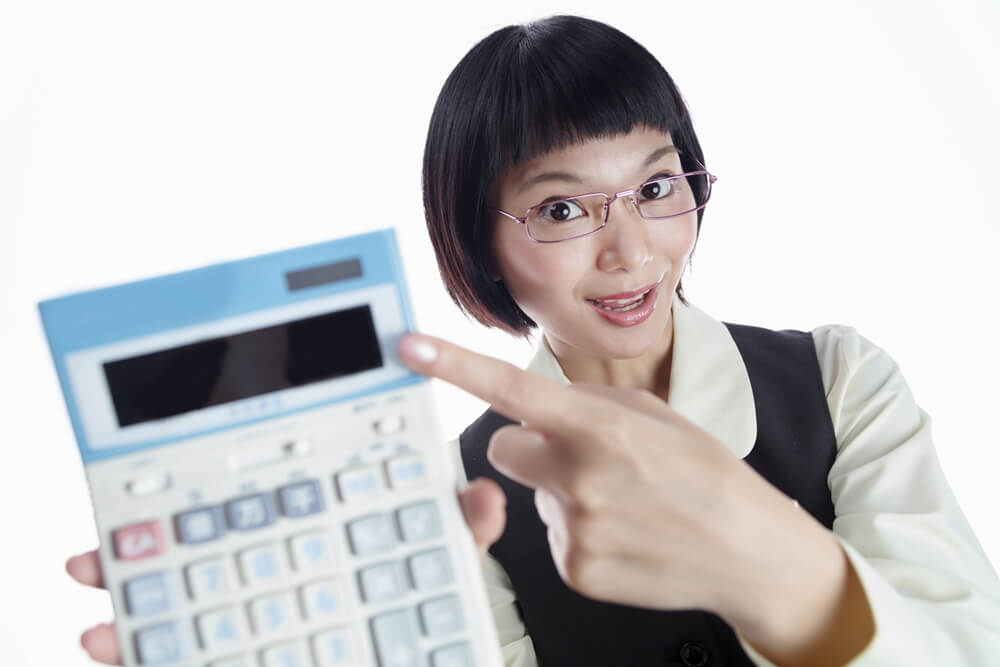 計算機を指差している眼鏡をかけたOLさんの写真