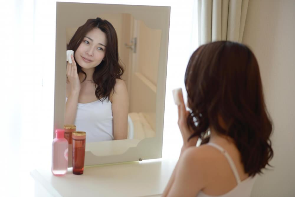 鏡を覗き込んでいるスキンケア中の女性